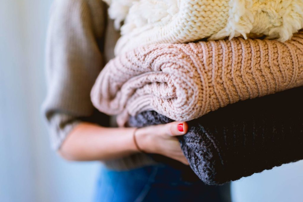 Konmari method for your money — a woman holds a stack of folded sweaters