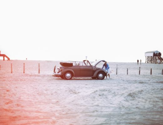 Driving a beater - Woman opens hood of a vintage car on a beach and peering into the engine