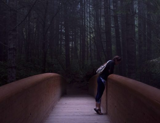 career break fail - woman stands on bridge in dark forest and looks down over the railing