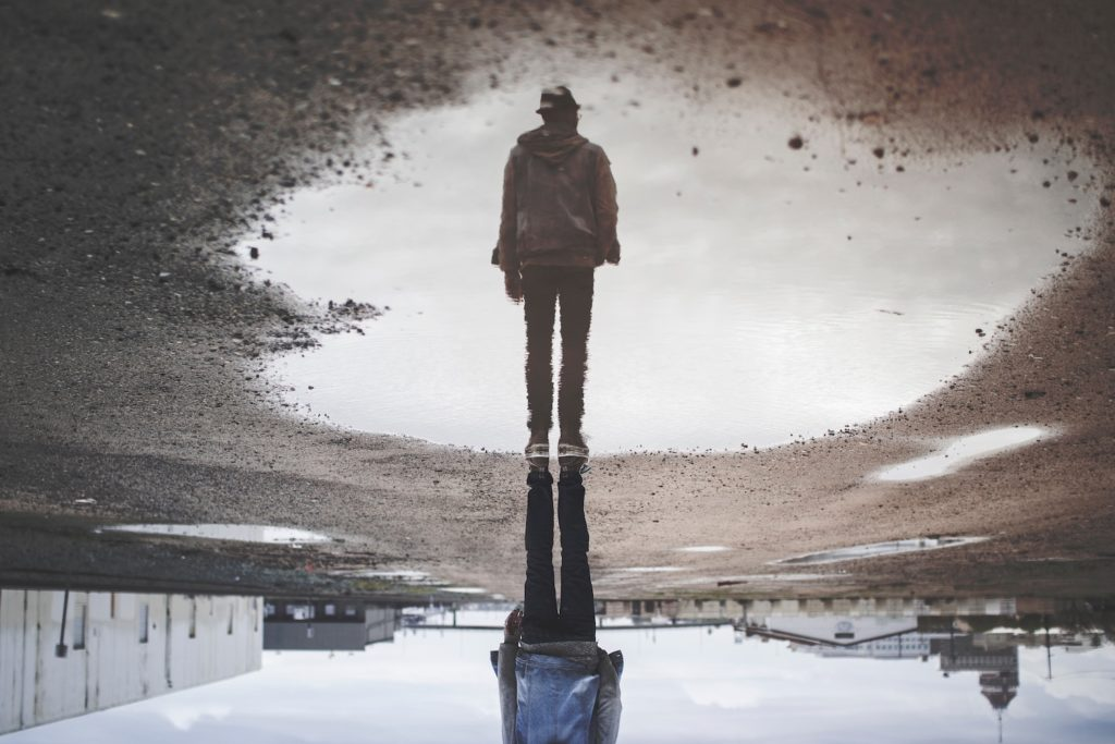 financial reality v fantasy - a man's reflection on a puddle, reversed so that his reflection appears to be standing upright