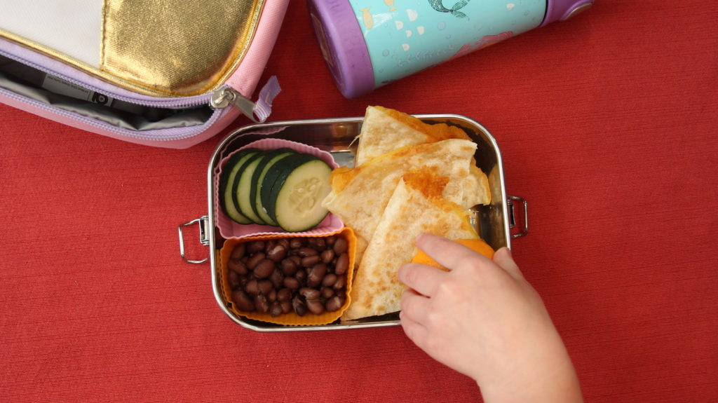 a lunch box sits open, and a child's hand reaches for an orange; 10-day school lunch menu