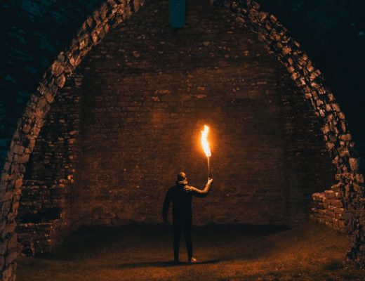 A man stands in a stone arch, holding a torch. optimizing for money or life.