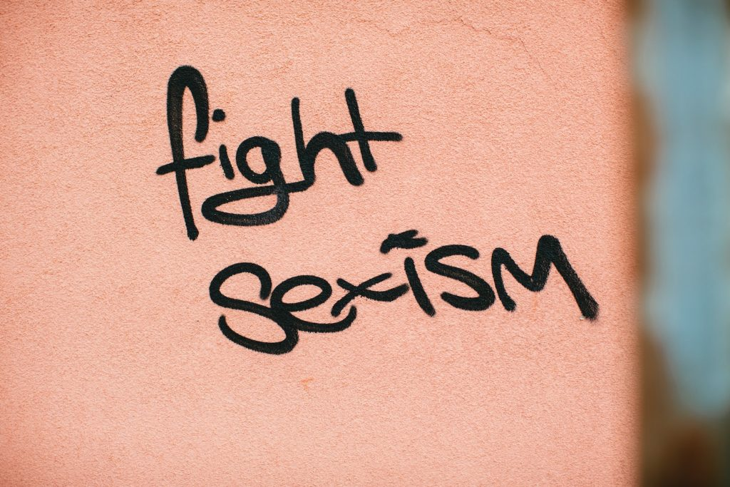"fight internalized sexism. The words ""fight sexism"" are spray painted in black on a light pink wall."