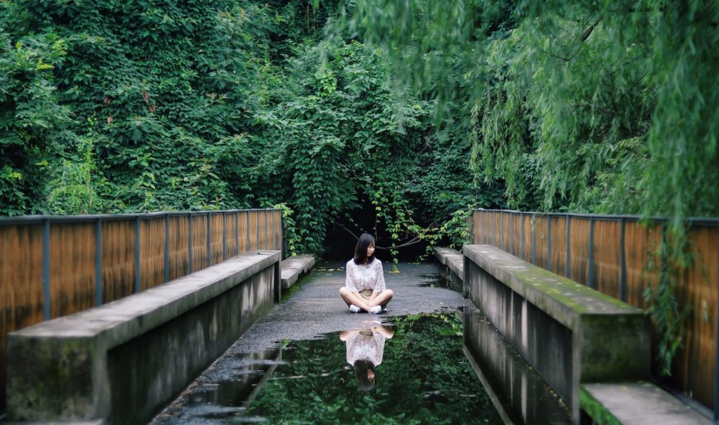A woman sits on a path surrounded by green foliage. A puddle in front of her reflects her image. Internalized sexism.
