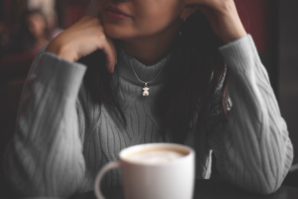 woman in grey sweater sits with latte, looking thoughtful. why the latte factor is a lie.