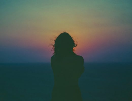 A woman stands alone on a beach, silhouetted by the setting sun. She hugs herself as her hair blows behind her. Post topic: how to deal with loneliness