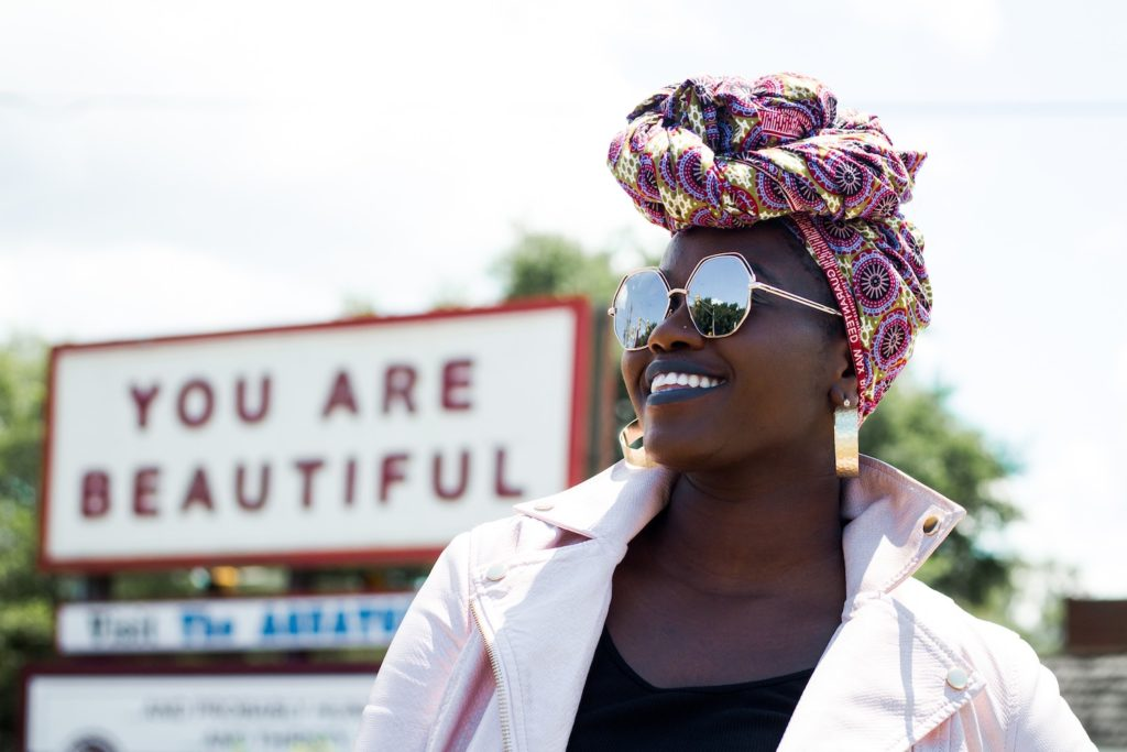 "A black woman with sunglasses and a colorful headscarf smiles, posing in front of a sign that says ""You are beautiful."" Be your own best friend."