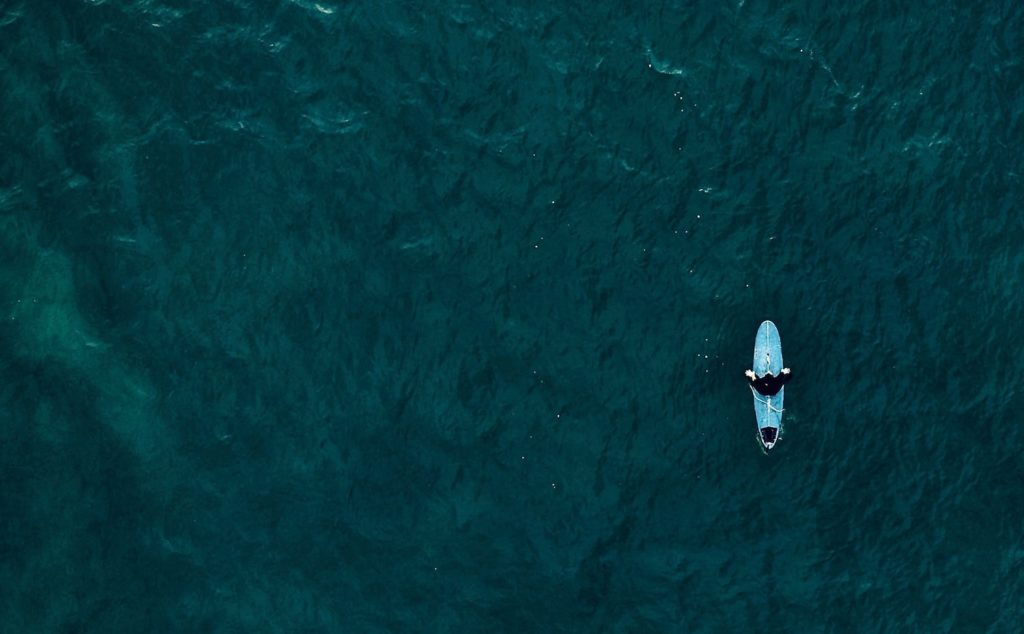 A surfer floats alone on waves, seen from above. how to deal with social isolation.
