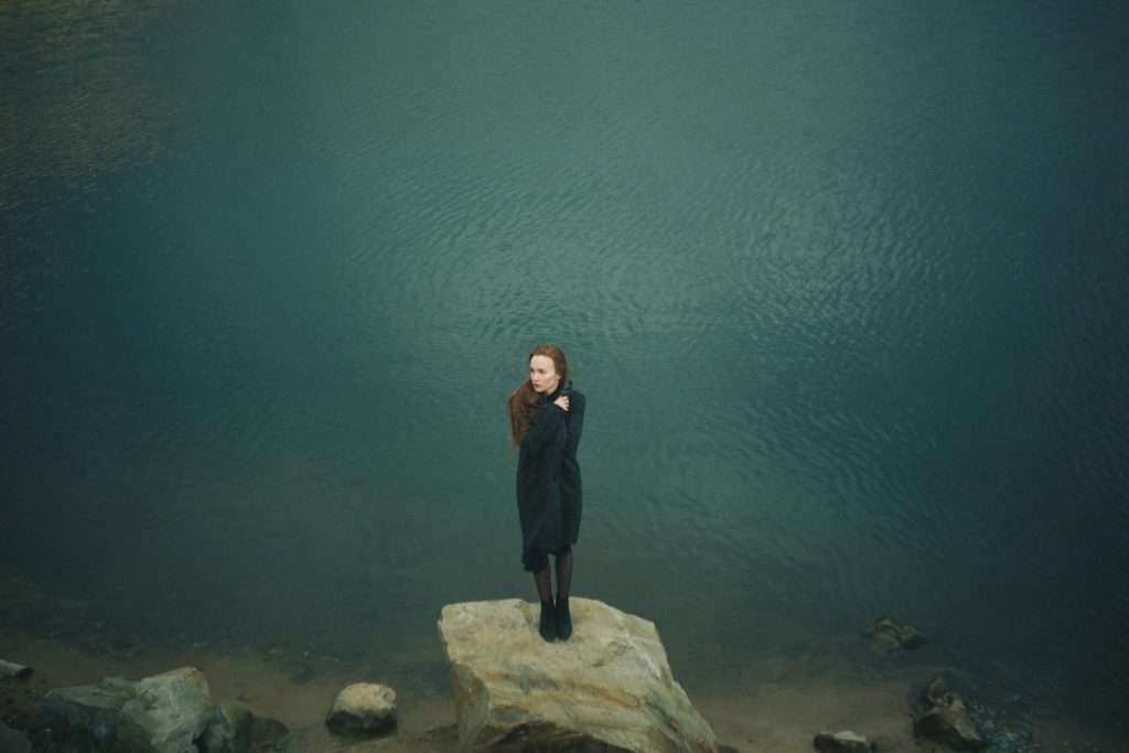 A woman stands small and alone on a rock in front of a body of water stretching out behind her, clothing a blanket to her body. grief in a pandemic