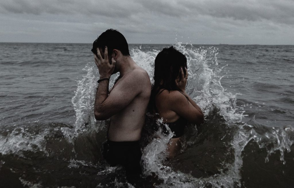 a man and woman face away from each other in a gray ocean, each holding their faces as if in frustration while a wave crashes against them