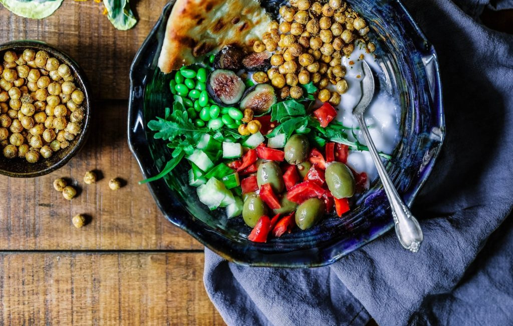 save money on a plant-based diet. A blue mediterranean bowl with olives, chickpeas, figs and a pita sits on a wooden table.