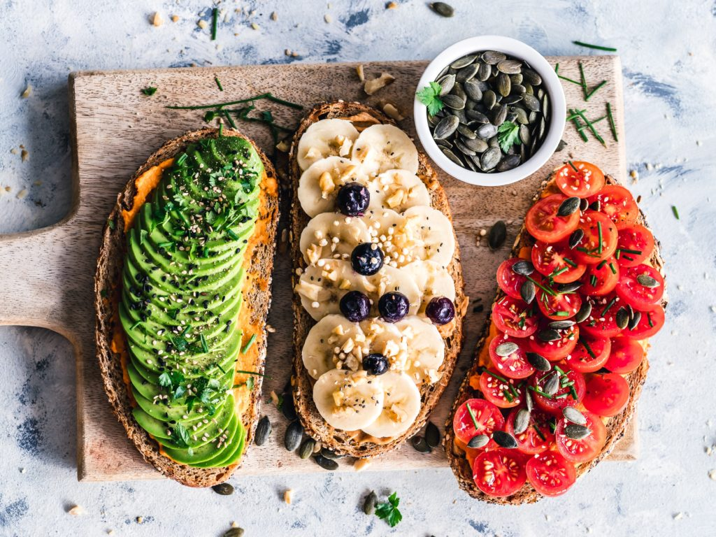 tips to save money on a vegan diet. three toasts sit on a wooden cutting board: an avocado toast, one topped with bananas and blueberries, and another topped with halved grape tomatoes and pumpkin seeds.